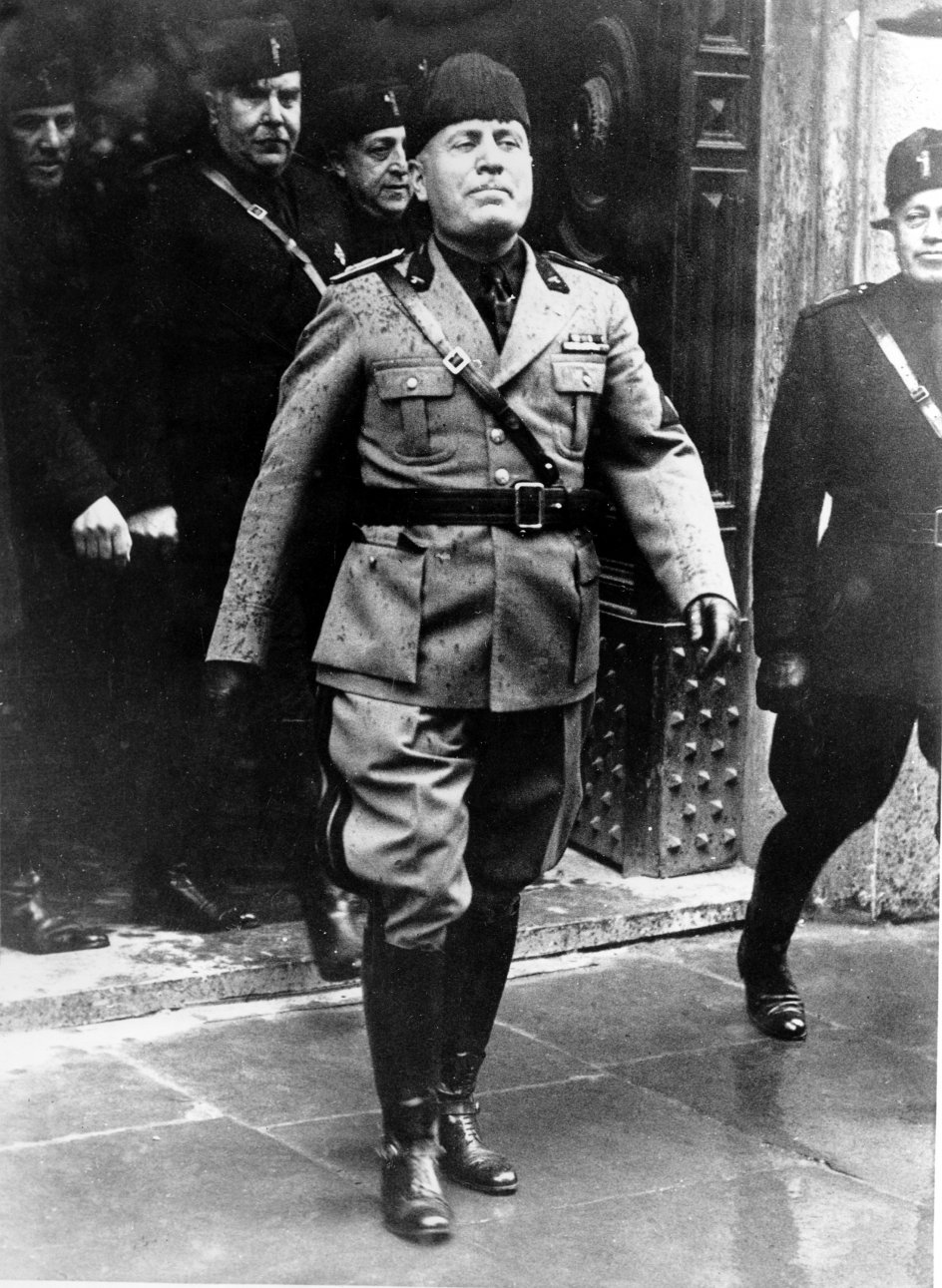 """FILE - In this April 21, 1936 file photo Benito Mussolini walks in the rain during the 2, 698th anniversary of the birth of Rome. A new documentary about Benito Mussolini examines the near cult-like fascination that Italians had with the fascist dictator and his body that continues today among his fans. """"Il Corpo Del Duce, """" (""""The Duce's Corpse"""") contains some gruesome, never-before-seen images of Mussolini's decayed corpse after he was hanged upside down in a Milan square on April 29, 1945 after being shot by anti-fascist partisans. The film, directed by Fabrizio Laurenti, is based on a book by Italian author Sergio Luzzato which literally follows the path of Mussolini's corpse from the gas station to a tomb in Predappio, his birthplace in northern Italy, where thousands of supporters still pay homage every year. (AP Photo/Str)"""