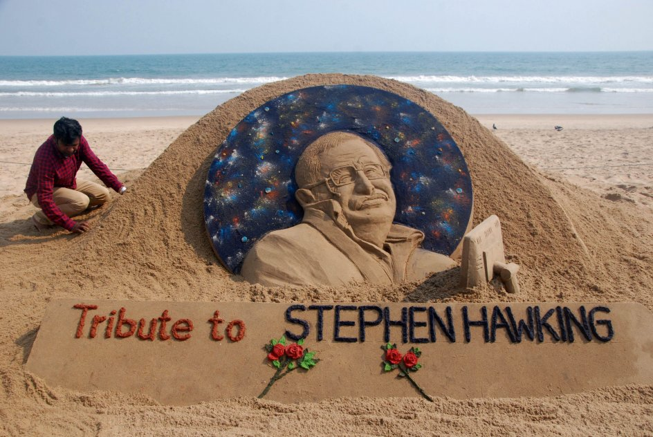 """TOPSHOT - Sand artist Sudarsan Patnaik gives final touches to a sculpture in honour of British physicist and award-winning author Stephen Hawking at Puri beach, some 65 kms. from Bhubaneswar on March 14, 2018. Renowned British physicist Stephen Hawking, whose mental genius and physical disability made him a household name and inspiration across the globe, died on March 14th aged 76. Propelled to superstardom by his 1988 book """"A Brief History of Time"""", which became an unlikely worldwide bestseller, Hawking dedicated his life to unlocking the secrets of the Universe. / AFP PHOTO / ASIT KUMAR"""