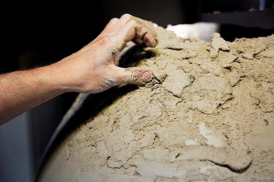 En kæmpekrukke er ved at komme til live i hænderne på en medarbejder på keramikværkstedet. Leret er blandet op med vinylfibre for at få den helt rigtige holdbarhed efter brænding – lidt på samme måde, som man i gamle dage blandede hestemøg med ufordøjede plantefibre i, fortæller Esben Lyngsaa Madsen. – Fotos: Carsten Bundgaard/Ritzau Scanpix.