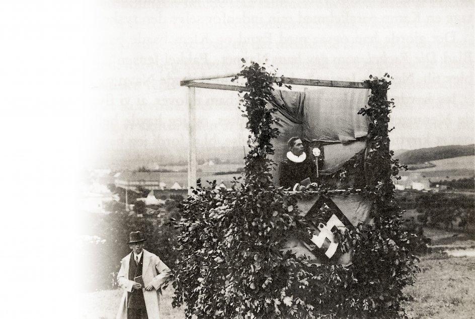 Anders Malling holder politisk tale iført præstekjole. Affoto fra bog.