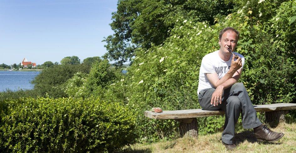 """Fra sit sommerhus i Kragevig på Sydsjælland har Knud Romer udsigt til Jungshoved Kirke, der """"står hvid og fin på den anden side af vigen med en lille havn"""", som han skriver i sin nye roman """"Kort over paradis"""". Det er også dér, han en dag skal begraves, fortæller han – tæt på fuglekvidder og barndommens Falster. –"""
