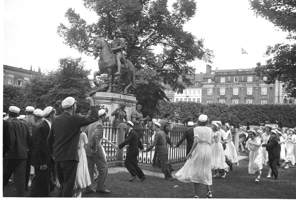 "Studenter fra Schnekloth' Skole danser omkring statuen på Kgs. Nytorv.;Newly fledged students are dancing the traditional rounds around the statue "" Krinsen "" on Kgs. Nytorv.;"