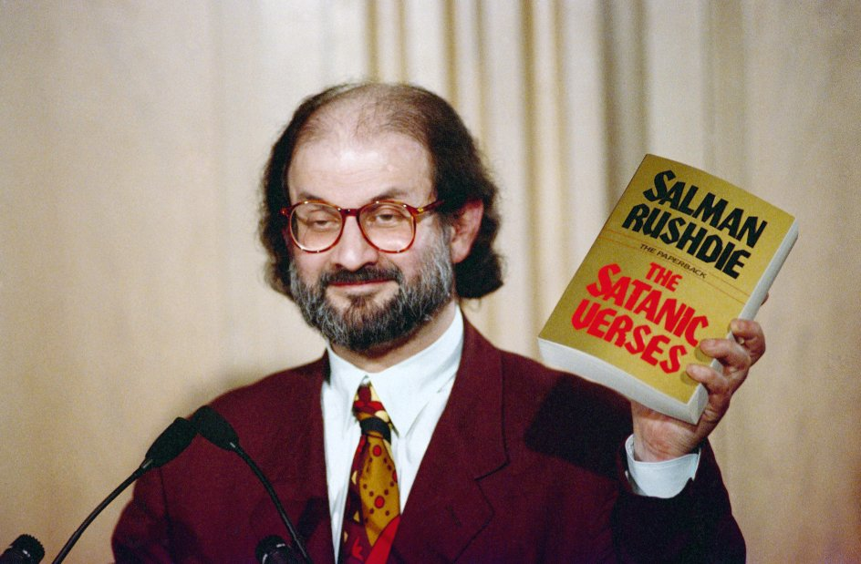 """Salman Rushdie holds up a copy of his book """"The Satanic Verses"""" at Freedom Forum in Arlington, Virginia in March 1992. (AP Photo/Ron Edmonds). Keywords: Standing Looking Away Holding Microphone Smiling Writer"""