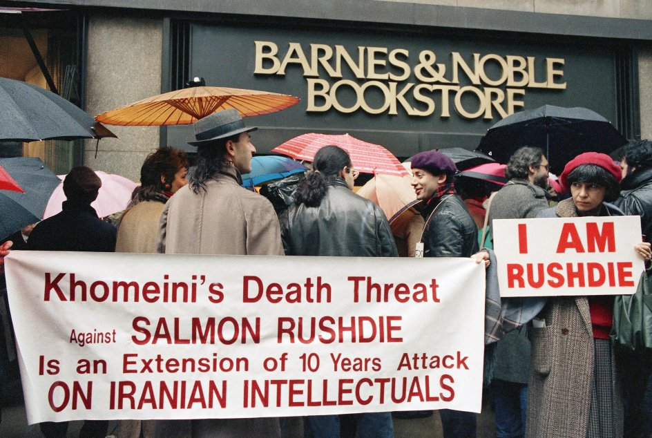 """People march outside a Barnes & Noble Bookstore in New York on Wednesday, Feb. 22, 1989 in protest of a decision store executives to remove copies of Salmon Rushdie's """"The Satanic Verses"""" store would become a target of violence after Iran's Ayatollah Khomeini threatened all those associated with the book. (AP Photo/David Cantor). Keywords: Banner"""