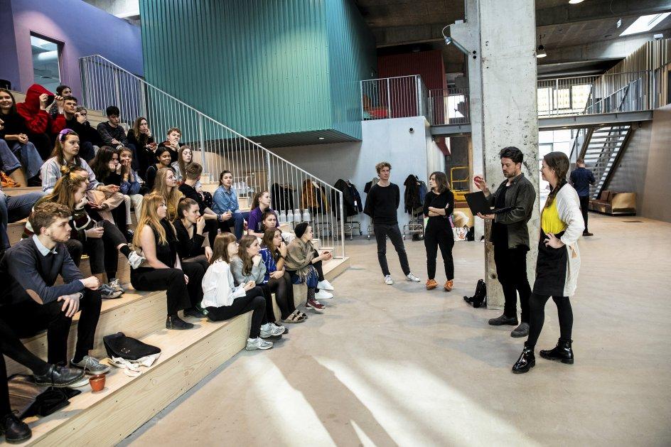 """Roskilde Festival Højskole er rykket ind i en gammel, totalt ombygget fabriksbygning. Her instruerer viceforstander Jonas Møller og musikeren Marie Højlund fra Nephew eleverne forud for opførelsen af indvielsessangen """"At dø er at rejse"""". -"""