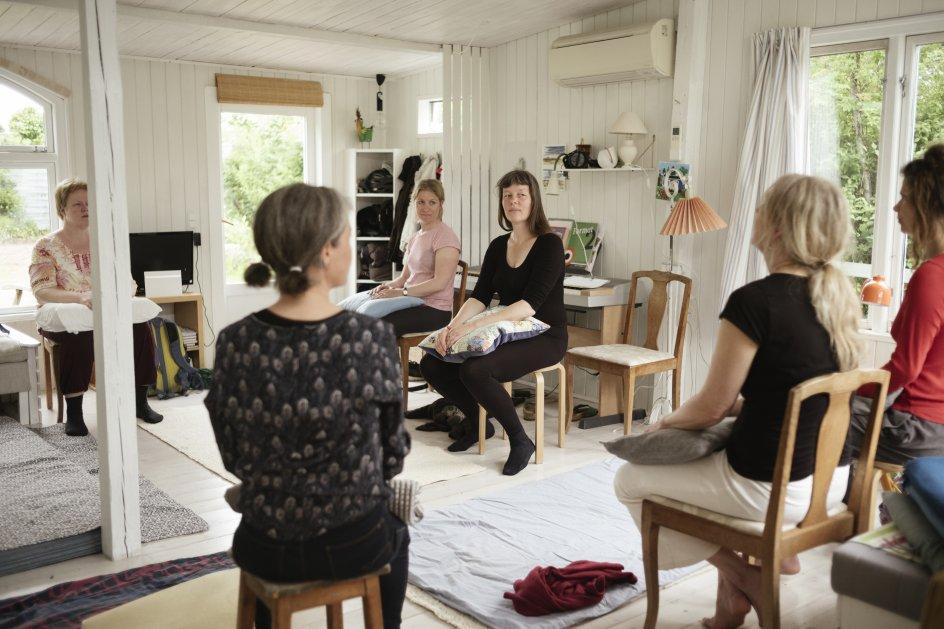 I sit haveforeningshus i Herlev underviser søvnkonsulent og leder af Søvnskolen Birgitte Hinz (med ryggen til nærmest kameraet) en gruppe kvinder i såkaldte mikrobevægelser. Små bevægelser, der skal berolige nervesystemet og gøre det nemmere at finde hvile og falde i søvn. Som mange andre danskere oplever de, at det kan være vanskeligt at finde roen i en hektisk hverdag. – Fotos: Asbjørn Sand.
