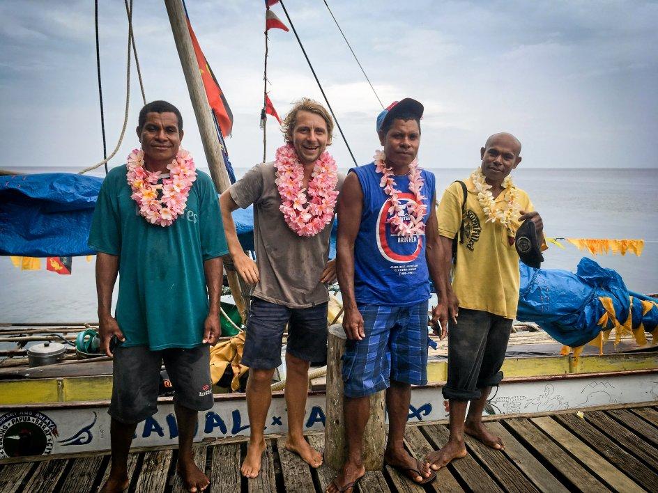 Skibets besætning hyldes efter at have passeret målstregen. Sammen med Thor Jensen står de lokale fiskere Justin John, Sanakoli John og Job Siyae. Sidstnævnte forlod ekspeditionen efter to måneder, men blev samlet op før målstregen. – Privatfoto.