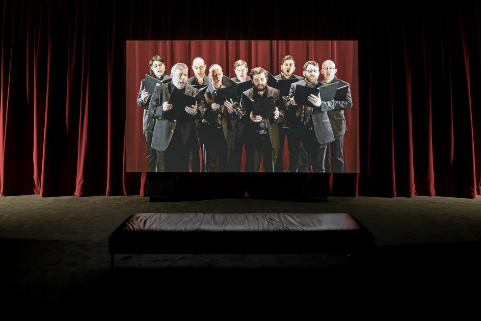 """I den sydafrikanske videokunstner Candice Breitz' storslåede todelte værk """"I'm Your Man"""" opleves først sangen sunget i et separat rum af koret fra Cohens synagoge i Montreal. I det store rum bagved, som er adskilt af et kæmpemæssigt, rødt forhæng, kan på 18 forskellige monitorer høres 18 mænd i alderen 65-plusserne synge sangene fra Cohen-albummet """"I'm Your Man"""". – Foto: Guy L'Heureux."""
