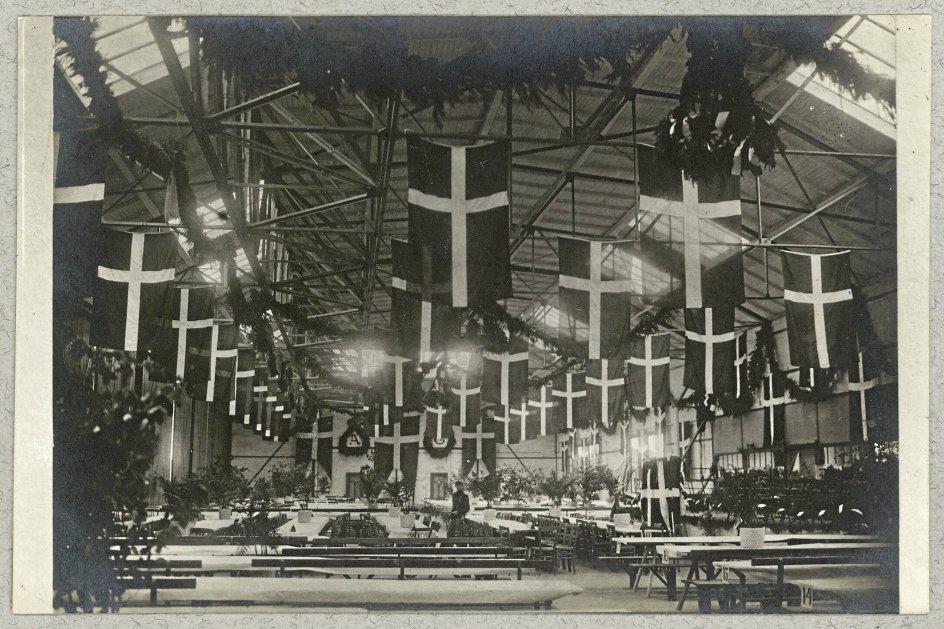 Sjældent før eller siden er der blevet flaget så meget med Dannebrog som ved Genforeningen i 1920. Her er en hal gjort klar til genforeningsfest. - Foto: Johs. Timm/Det Kongelige Biblioteks Billedsamling.