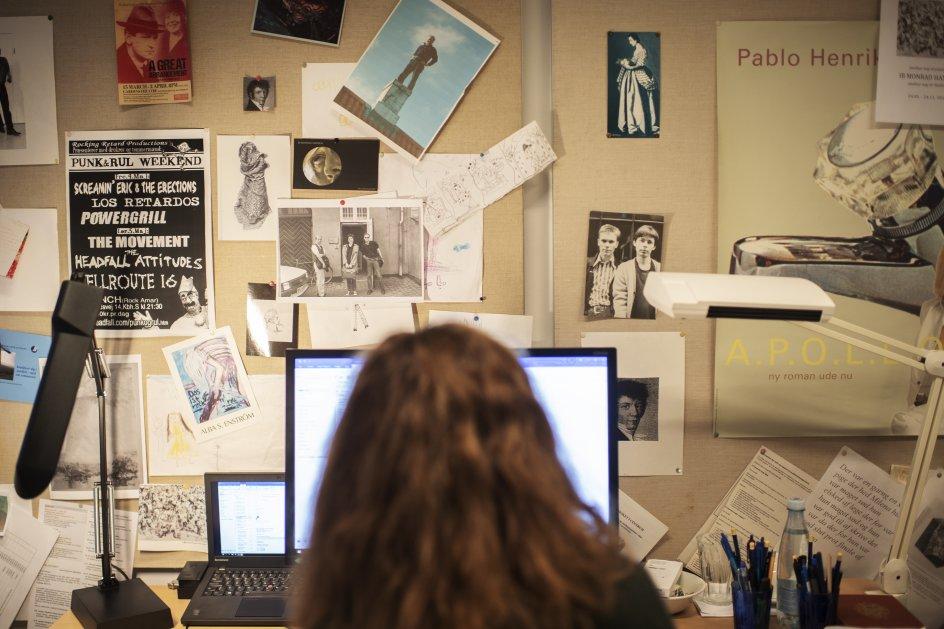 På opslagstavlen over Marianne Stidsens skrivebord på Københavns Universitet hænger blandt andet beviser for lektorens fortid i punkmiljøet og en plakat for en bog af Pablo Llambias (uden for billedet viser plakaten et par bare bryster). – Foto: Julie Meldhede Kristensen.