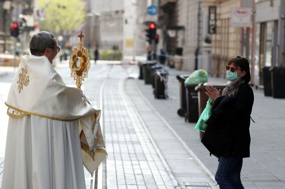 En præst velsigner en kvinde påskesøndag i den næsten tomme bymidte i Zagreb, Kroatien. Foto: Damir Sencar/AFP/Ritzau Scanpix
