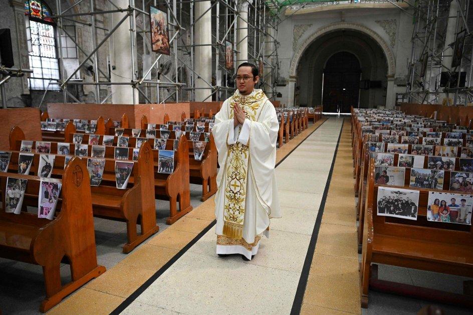 En katolsk præst går gennem en tom kirke i Filippinerne inden et optog i Angeles City påskesøndag. På kirkebænkene hænger billeder af kirkens sognebørn. Foto: Ted ALJIBE / AFP