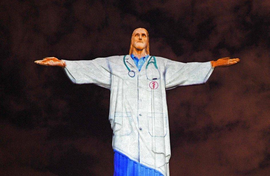 Den ikoniske 38 meter høje kristusstatue i Rio de Janeiro, Brasilien, var påskesøndag oplyst, så det lignede, at statuen var iført lægekittel. Foto: Carl De Souza/AFP/Ritzau Scanpix