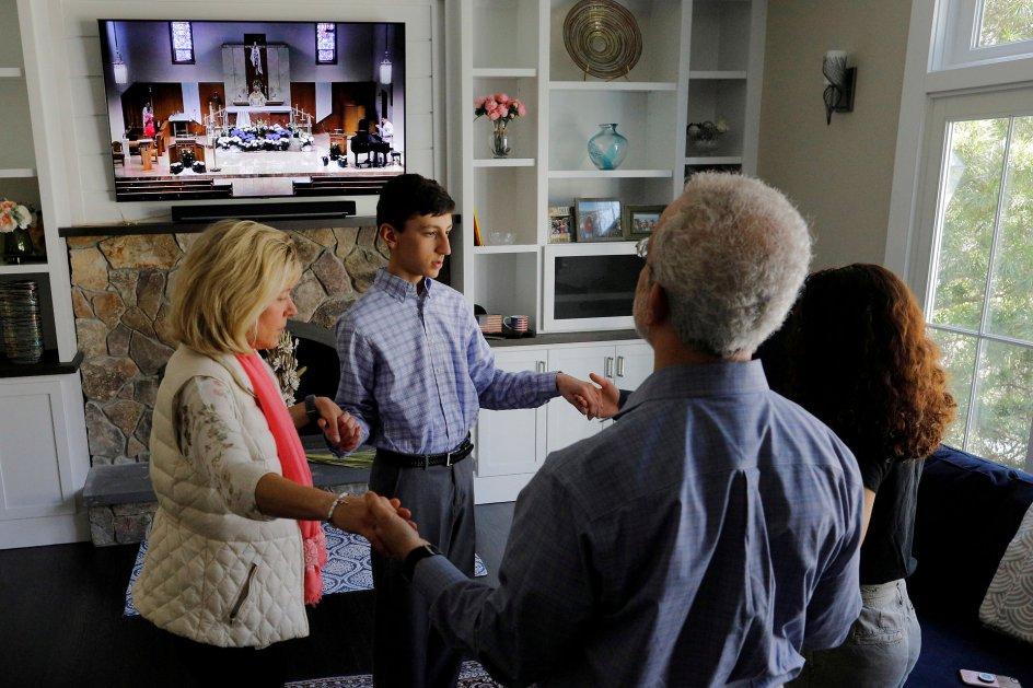 En familie tager del i en katolsk påskegudstjeneste, der livestreames til deres hjem i Massachusetts, USA, påskesøndag. Foto: Brian Snyder/Reuters/Ritzau Scanpix