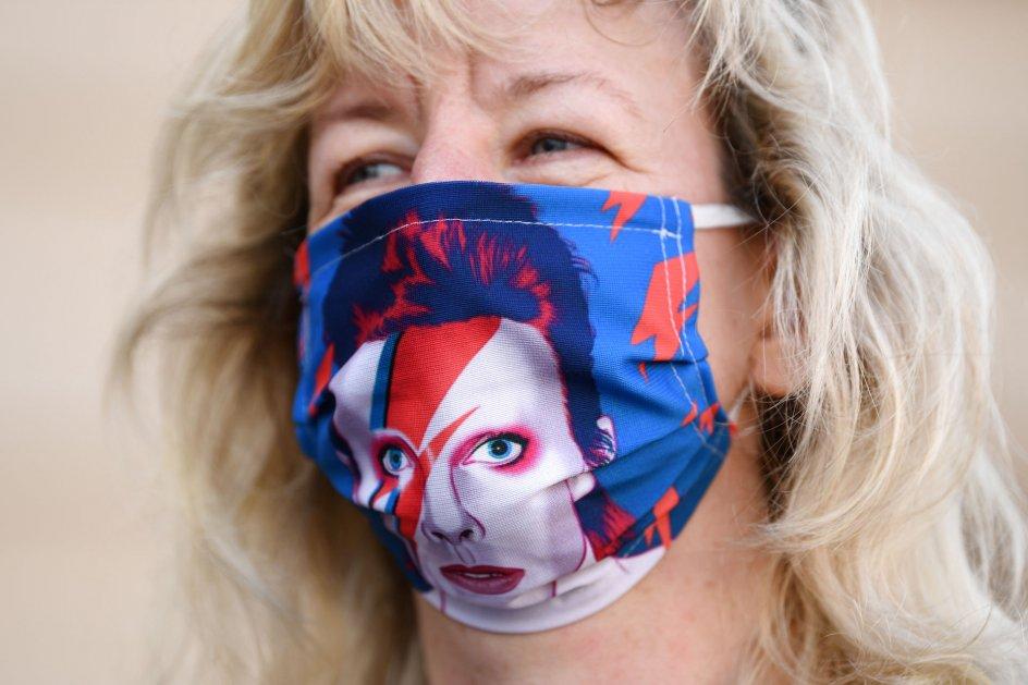 En kvinde i Berlin bruger et genanvendeligt stofmundbind med et billede af David Bowie.