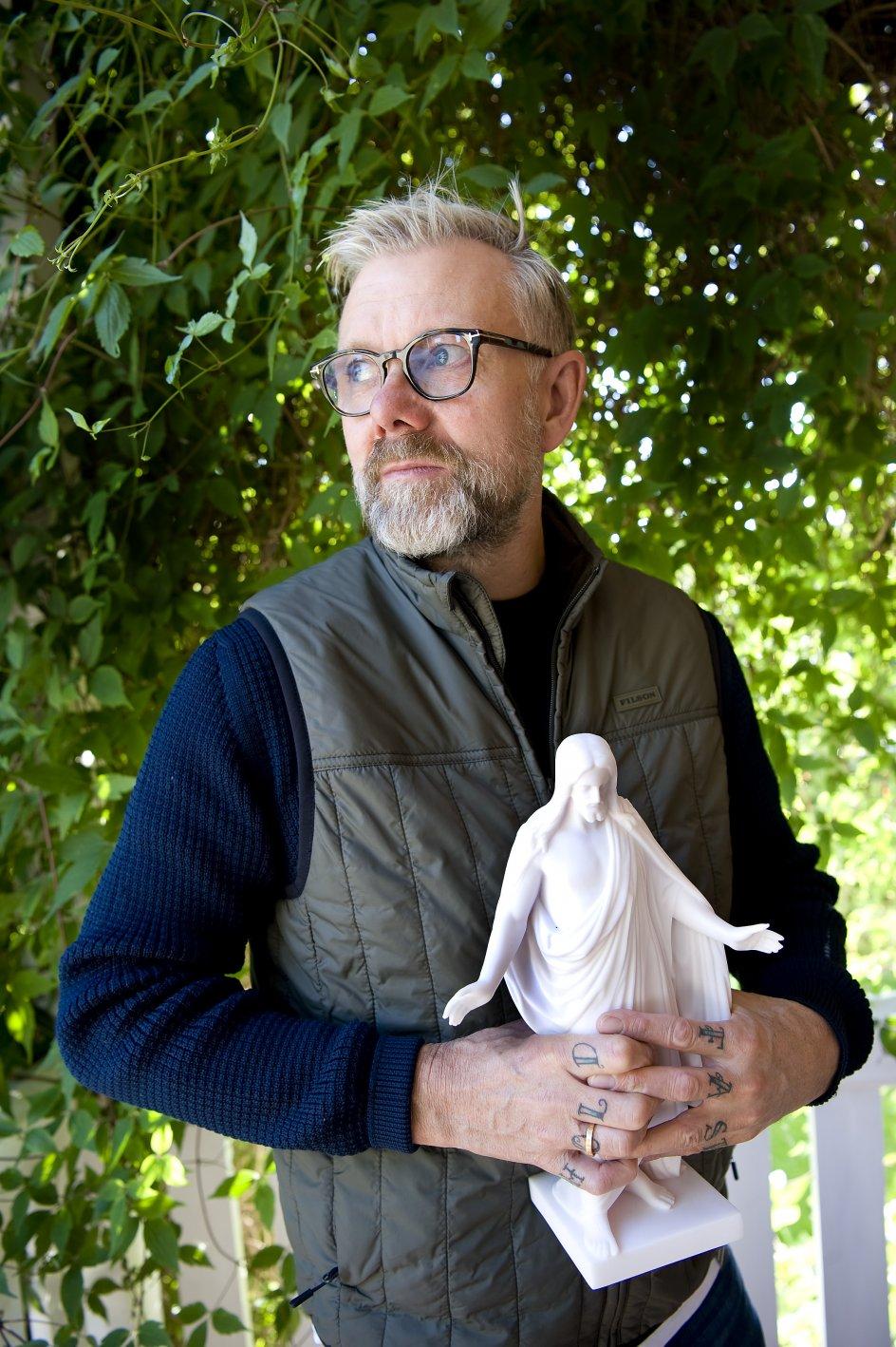 """Thorvaldsens Kristus var en gave til Casper Christensen, da han blev døbt i august. I forbindelse med sin eksistentielle oprydning har han fået tatoveret den gamle sømandstatovering """"Hold fast"""" på otte fingre. Nu vil han have tatoveret et kors som et udtryk for det kærlige nærvær, han erfarer. – Foto: Leif Tuxen."""