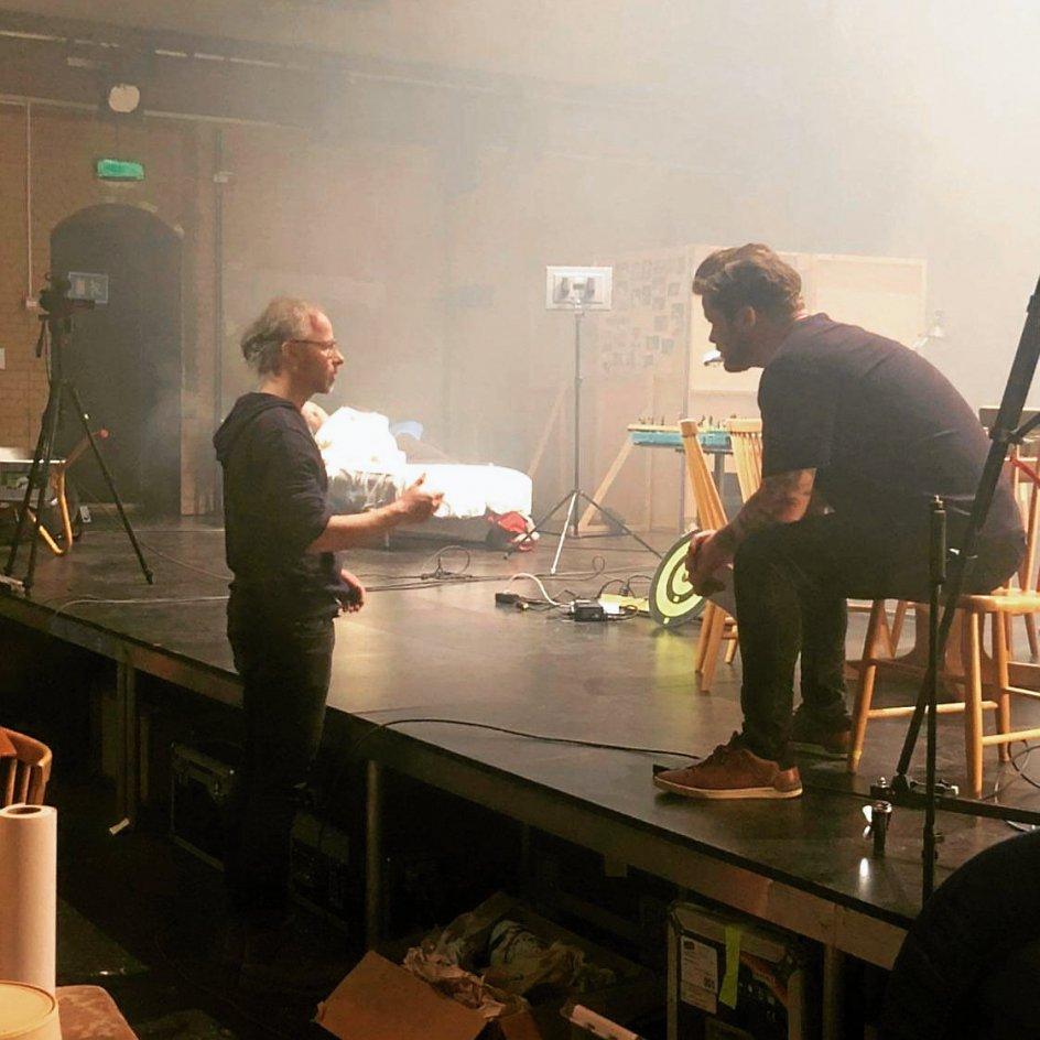 Palle Würtz sidder på scenen i en pause under prøverne i samtale med instruktøren Tue Behring. – Privatfoto.