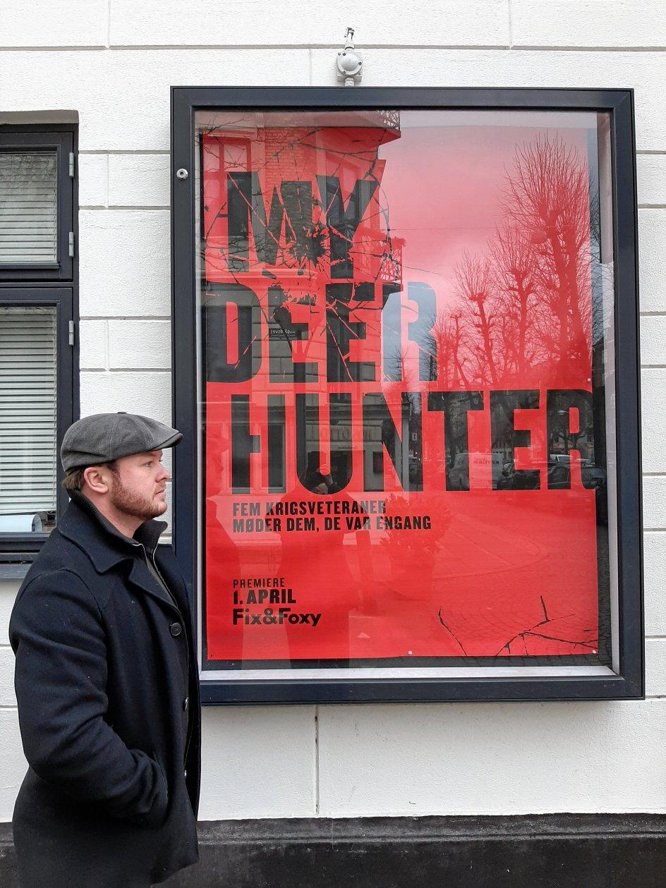"""Palle Würtz fotograferet foran plakaten for """"My Deer Hunter. Dog før coronakrisen og nye spilledatoer. – Privatfoto."""