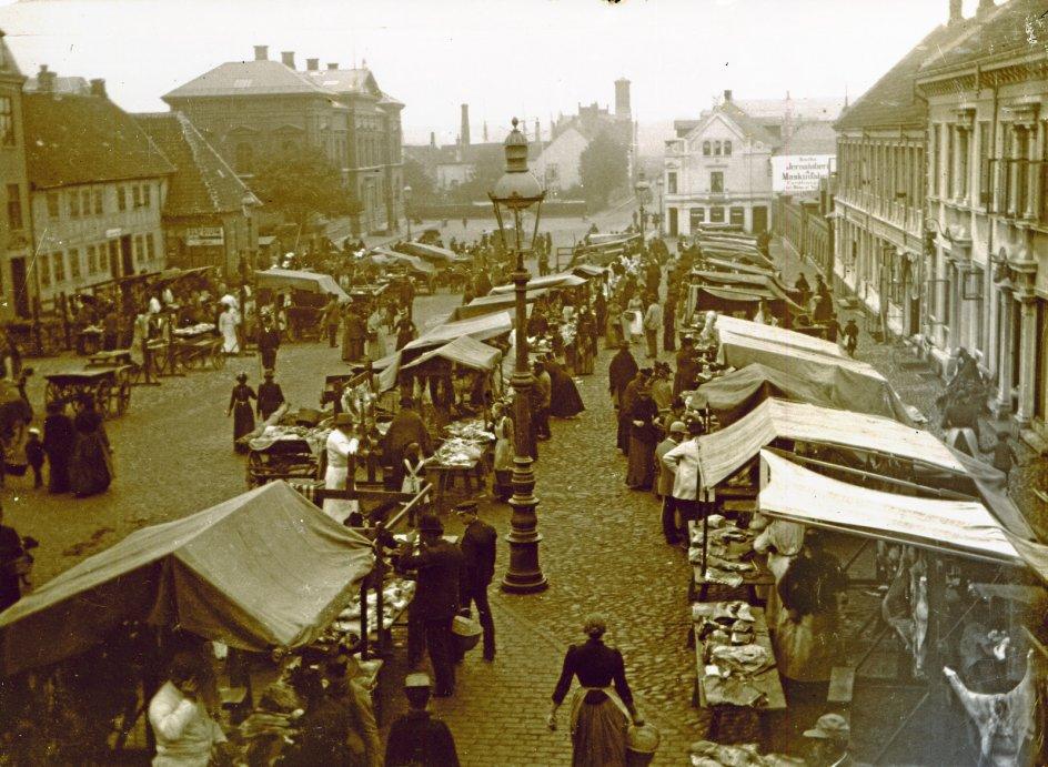 Indtil slutning af 1800-tallet solgte byens slagtere og fiskehandlere deres vare på Frederiksplads i Randers. Båder koner og piger hjalp til i boderne. – Foto: Randers Stadsarkiv.