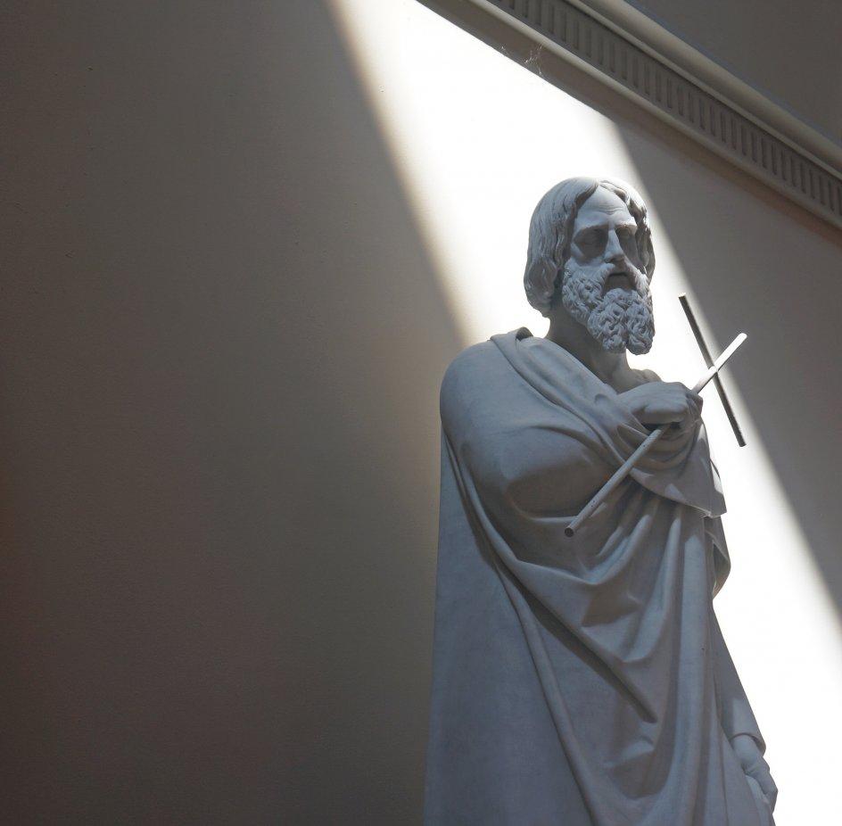 """Dette billede er taget på en halvskyet dag til gudstjeneste i Københavns Domkirke. Fotograf Helle Olsen skriver: """"Pludselig brød solen frem og dannede motiv med lys og skygge. Lyset sender sine stråler ned over Apostlen Philip, der trofast står med sit jernkors."""""""