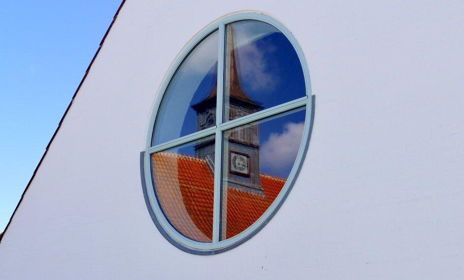 På dette billede har fotografen fanget spejlingen af Hornbæk Kirke i sognehusets vindue.