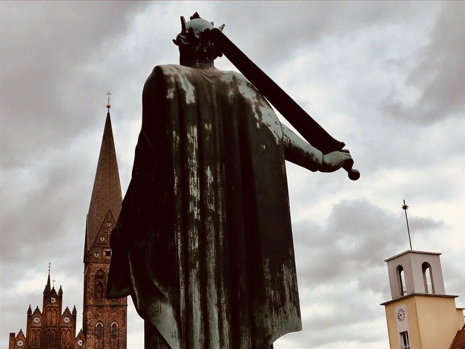 På billedet ses statuen af Knud den Hellige med ryggen til Odense Domkirke og front mod Skt. Albani Kirke, skriver fotografen. Knud den Hellige var konge af Danmark fra 1080 til 1086 og ligger begravet ved Odense Domkirke, som også hedder Sankt Knuds Kirke.