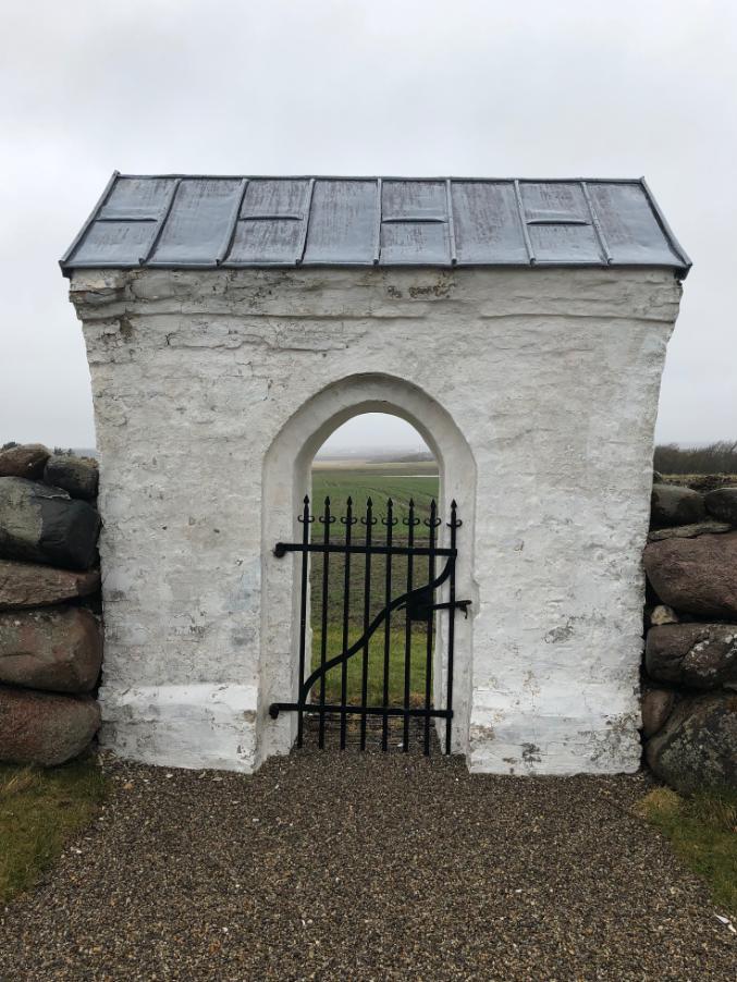 På dette billede ser man udgangen fra kirkegården ved Jannerup Kirke i Thy mod en overskyet himmel.