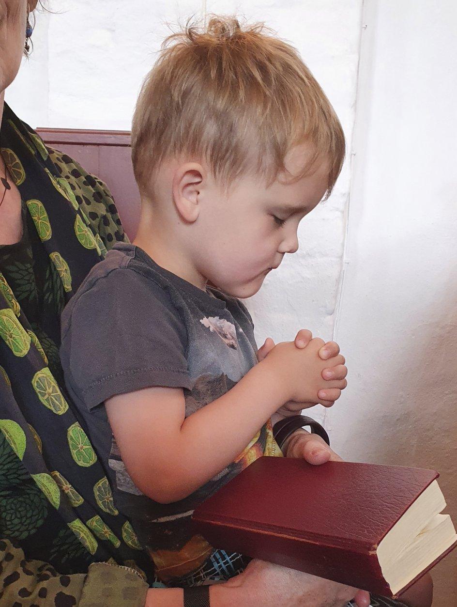 """I Fanefjord kirke på Møn spørger Anders nysgerrigt sin morfar """"hvorfor har du lukkede øjne? """" Dernæst lukker han øjnene og gør som Morfar. Foto: Gunnvá Bak Mortensen"""