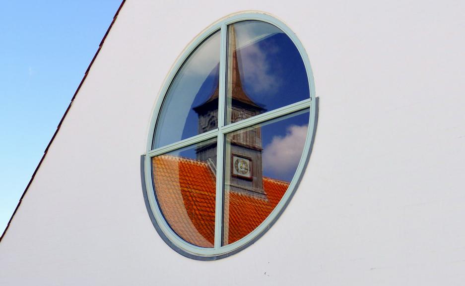 Hornbæk kirke stod skarpt i sognehusets vinduer. Foto Kim John Andersen
