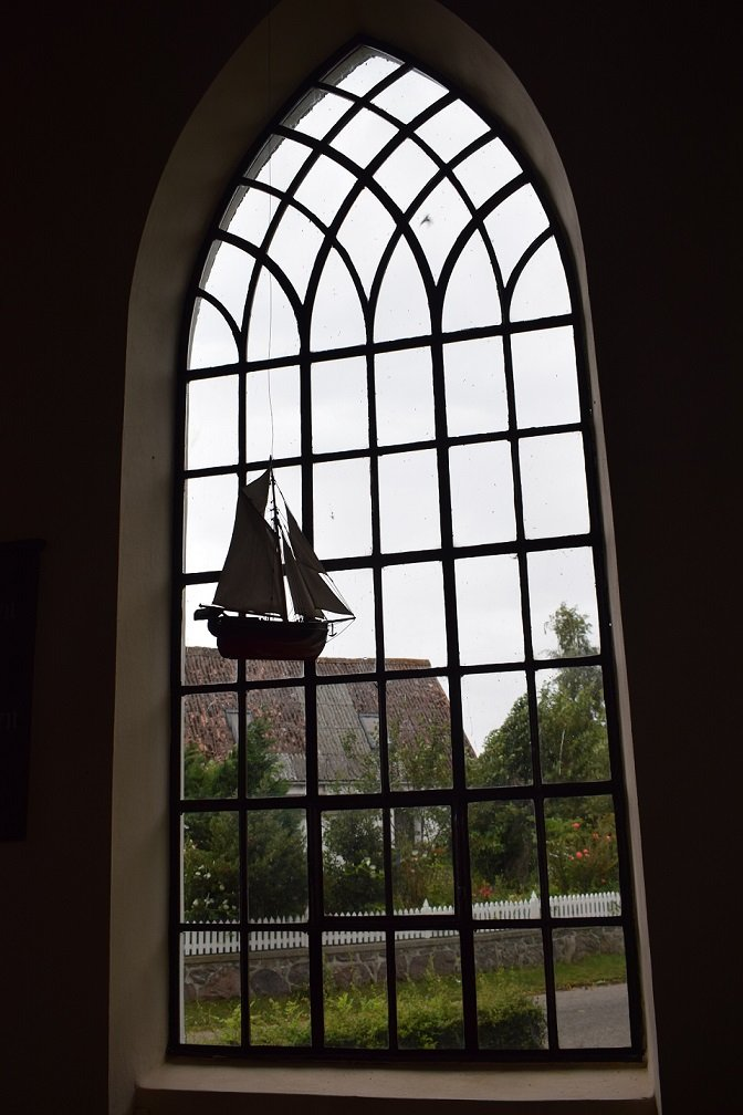 """Her ses et billede fra sidste års udgave af konkurrencen """"Med troen på ferie"""".  Om billedet skriver fotografen: """"For mig emmer det her billede af guddommelighed. Aftensolen, som giver den summende mark en varm magisk farve, som kontrast til den kølige blå himmel og midt i ligger kirken, hvor de to mødes."""""""