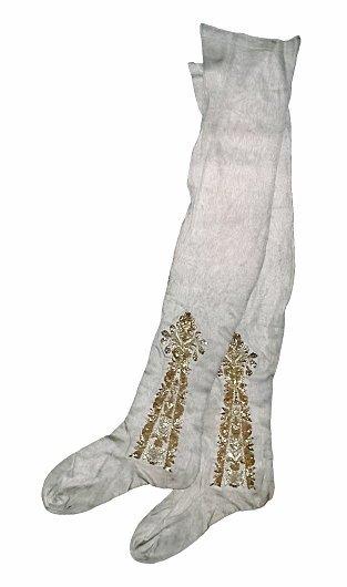 """De guldbroderede, maskinstrikkede (!) strømper er del af Christian den Syvendes salvingsdragt i hvid og guld fra 1767. – Foto fra bogen """"Ti kongers tøj""""."""