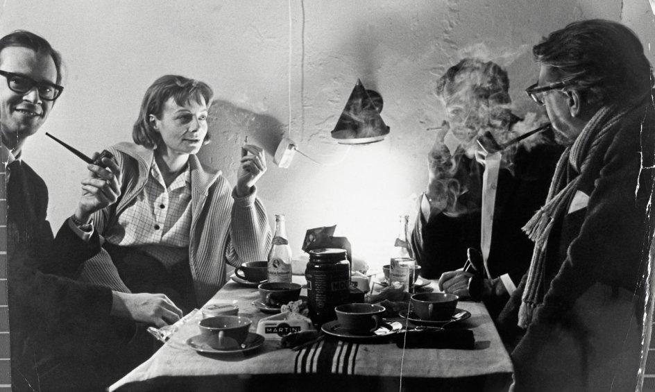 I dag tales der om røgfri arbejdspladser. Den betegnelse passede ikke på Statens Husholdningsråd, den første statslige forbrugerorganisation i verden, der blev oprettet i 1935. Her testede man også kvaliteten af cigaretter (øverst). Det kunne være nok så nyttigt, for der blev storrøget ude i de små hjem. På det nederste billede ses skuespillerne Ingolf David og Birgitte Federspiel samt instruktøren Søren Melson og en fjerde person, der er indhyllet i tobakståger.