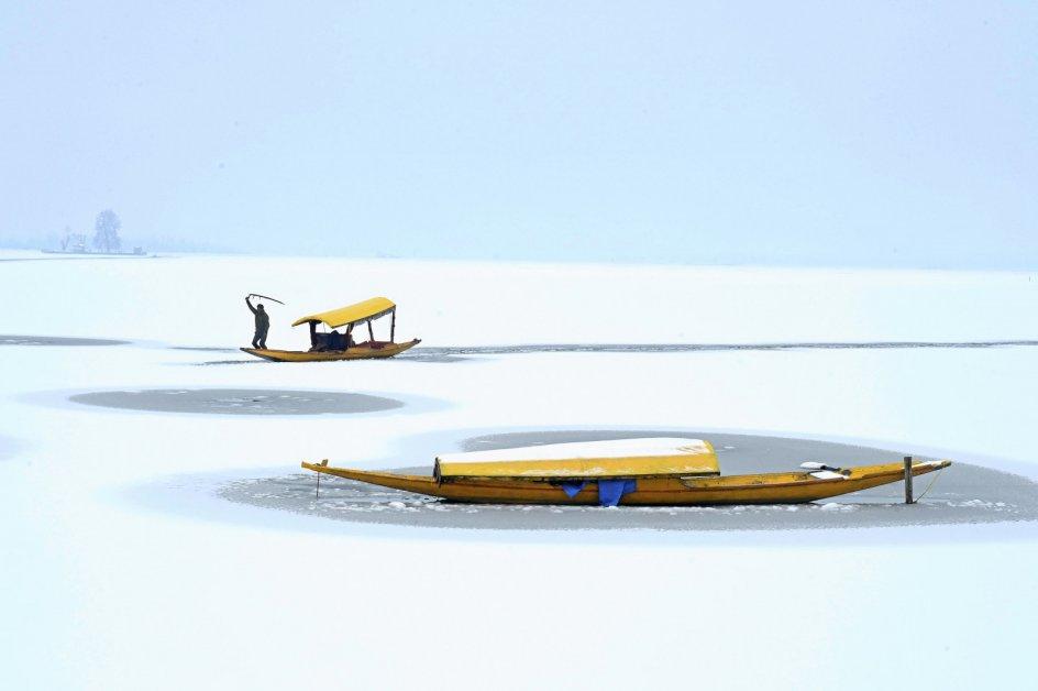 Om sommeren udgør byen Srinagar, hvor billedet er taget, hovedstaden i Indiens nordligste delstat, Jammu og Kashmir. På denne tid af året er det dog langt fra sommer, og lokale bådmænd har fået til opgave at navigere i den delvist frosne sø. Foto: Tauseef Mustafa/AFP/Ritzau Scanpix.