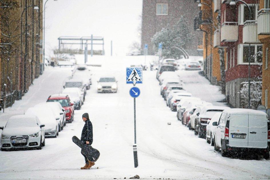 """""""Snö"""" siger vores naboer mod øst om de hvide fnug, der ikke så sjældent daler fra himlen hos dem. Her krydser en mand gaden i Sundbyberg nær Stockholm, mens en snestorm i sidste uge var i gang. – Foto: Jonathan Nackstrand/AFP/Ritzau Scanpix."""
