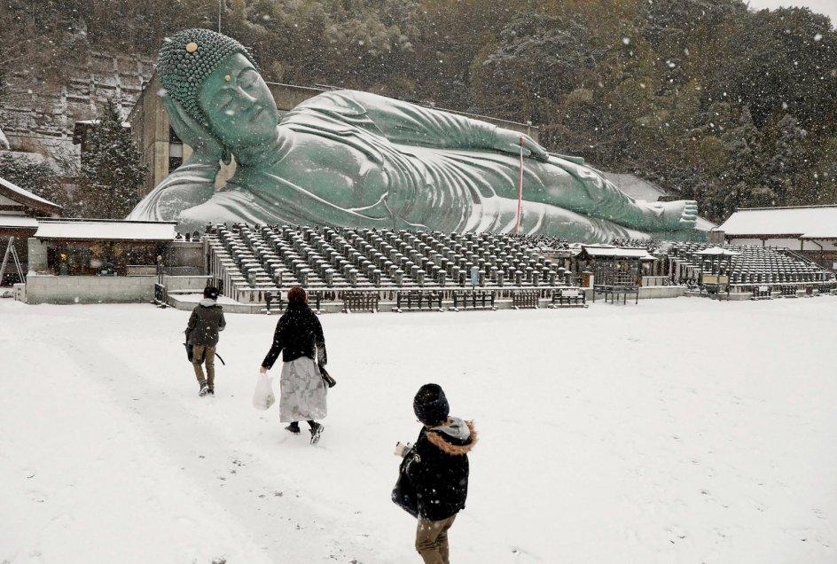 Foran det buddhistiske tempel Nanzoin, der ligger i den japanske by Sasaguri, er den liggende Buddha-statue blevet beklædt med et snetæppe. Med en længde på 41 meter og en vægt på knap 300 tons siges den at være verdens største bronzestatue. – Foto: AFP/Ritzau Scanpix.