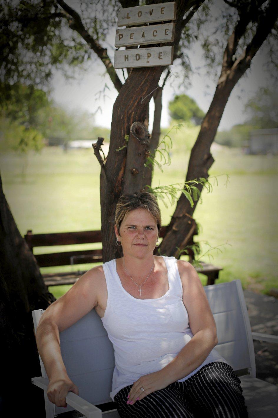 """Trods et succesrigt liv i politiets tjeneste er Lynda Steyn ikke blevet forfremmet i 22 år. """"Det er jo, fordi jeg er hvid. Men jeg lever og ånder for mig job,"""" siger hun her i familiens have. Familien har ord hængende som udsmykning, ingen billeder. Det er meget almindeligt blandt Sydafrikas boere, som er præget af den calvinistiske tro."""