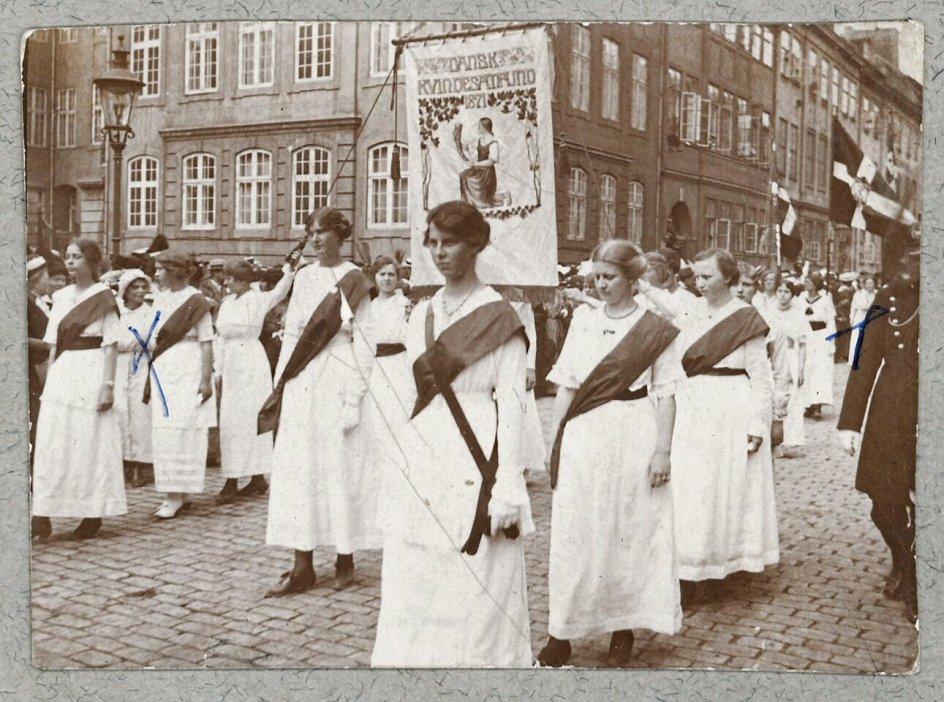 En lang række kvindeorganisationer gik i 1915 i det berømte kvindetog til Amalienborg for at markere over for kongen og hele befolkningen, at kvinder nu havde del i borgerrettighederne. Her ses Dansk Kvindesamfunds repræsentanter med foreningens fane. – Foto: Det Kongelige Biblioteks Billedbasen.