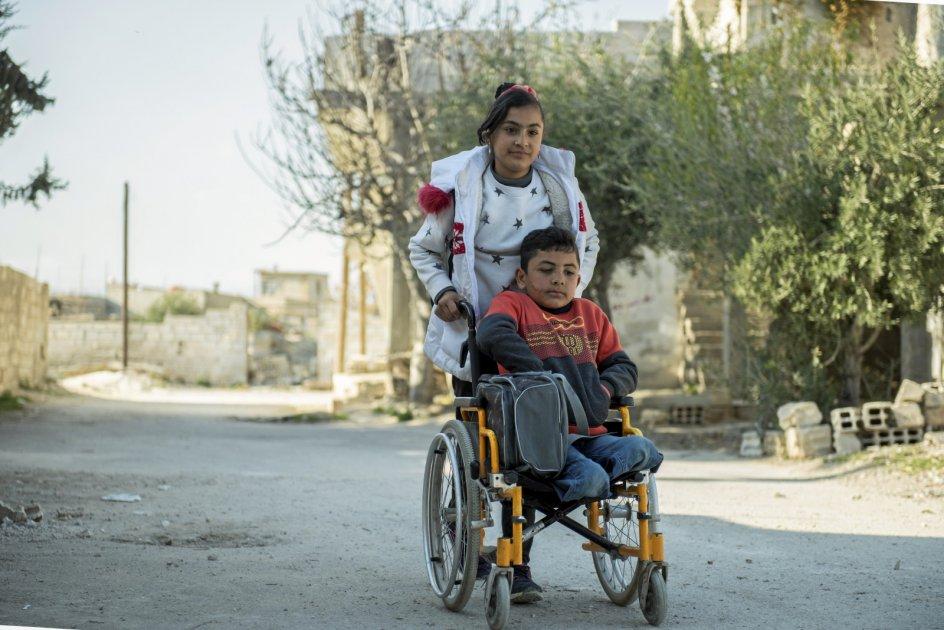 Bashar mistede sine ben for tre år siden i en bombeeksplosion og får hjælp af sin storesøster, når han hver dag skal til og fra skolen. – Foto: Hasan Belal.