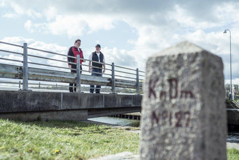 Grænseentusiasterne Hans Peter Nissen (tv.) og Peter Tagesen (th.) på broen over indløbet ved Hejlsminde Nor. Før Genforeningen i 1920 gik grænsen lige præcis midtfor broen, der dengang ikke var bygget. Man skulle med en færge over for at komme til Danmark, og det lykkedes Hans Peter Nissens morfar, der i 1916 flygtede fra tysk militærtjeneste.