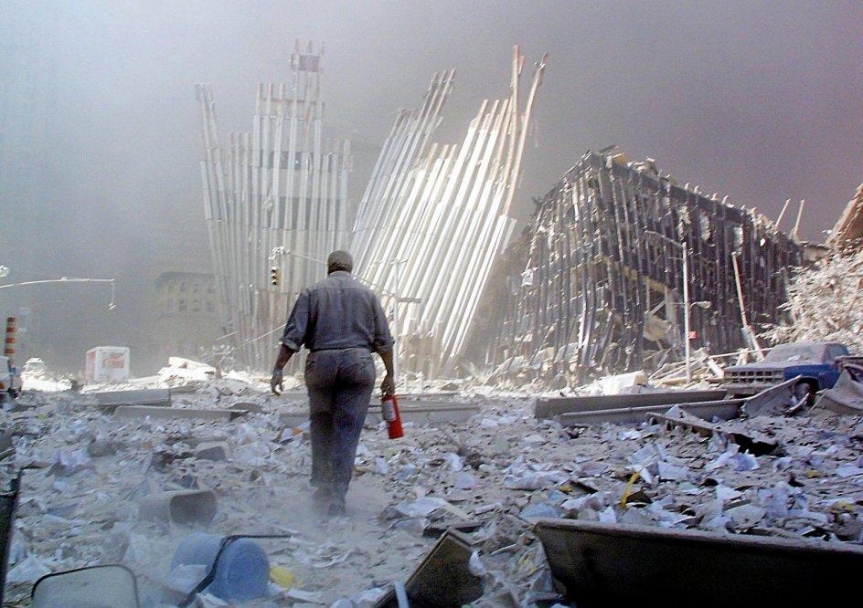 En mand går med en skumslukker, efter at den første af de to skyskrabere er faldet sammen om morgenen den 11. september 2001. Straks fra begyndelsen blev datoen synonym med begivenheden. I USA sædvanligvis forkortet 9-11. —