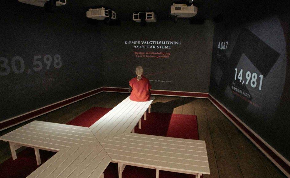 Den er del af en udstillingsarkitektur, der er værd at hæfte sig ved. En lille rød ramme er hele tiden med til at antyde det danske flag, en grå mimer de danske uniformers farve. Ved installationen danner de hvidlakerede bænke på det røde tæppe simpelthen det dannebrog, man sidder på. – Foto: Museum Sønderjylland.