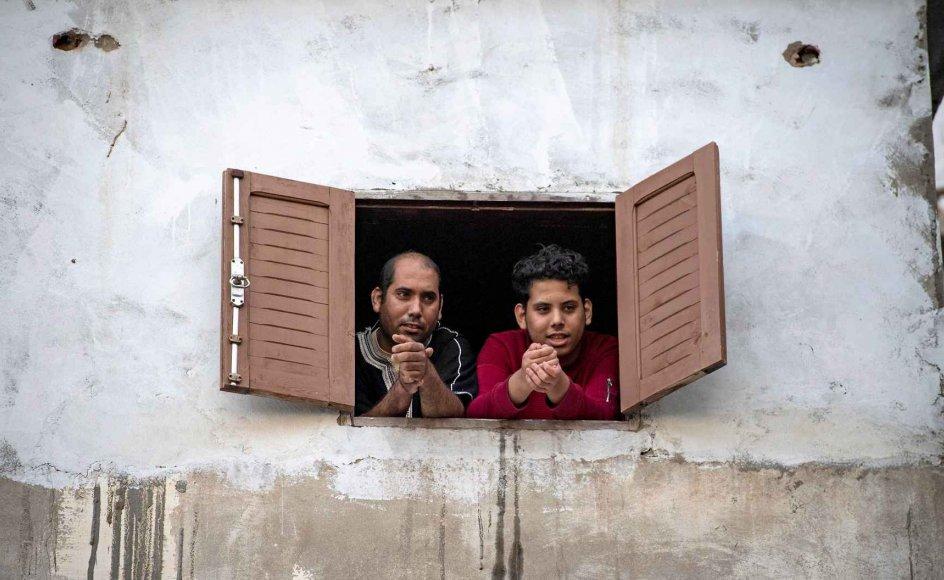 Over hele verden har lokale myndigheder bedt deres borgere om at holde sig inden for hjemmets fire vægge for at begrænse smitten af coronavirus. Her er det en marokkansk far og søn, der ser ud på gaden fra deres vindue i Takadoum-distriktet i hovedstaden, Rabat.