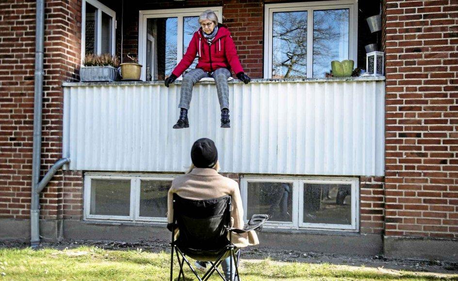 Siden den 5. marts har Judith Langergaard isoleret sig i sin lejlighed i en boligblok i Odense på grund af angst for smitte med coronavirus. Hver dag kommer hendes datter Louise forbi og taler med sin mor på græsset foran altanen. – Foto: Tim Kildeborg Jensen.