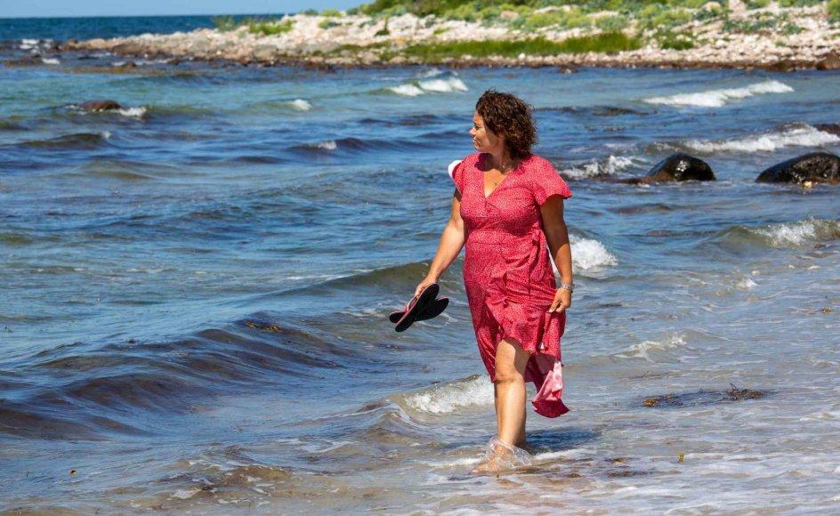 """Carina Jørgensen på stranden ved Nekseløbugten på Vestsjælland. Her var hun for to år siden nær ved at drukne. Oplevelsen blev et vendepunkt, og hun besluttede sig for en såkaldt gastric bypass-operation og har siden tabt 46 kilo. I dag har hun sluttet fred med sin krop. """"Hvis man ikke får bearbejdet de psykiske faktorer, der ligger til grund for overvægten, så er det svært at holde et vægttab,"""" siger hun. – Foto: John Olsen."""