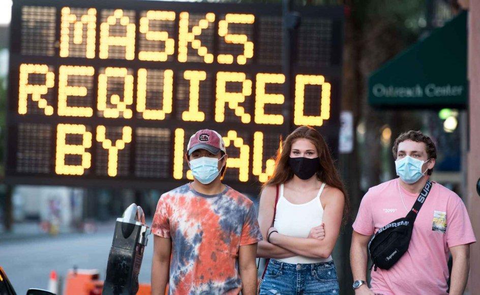 Stadig flere lande råder befolkningen til at iføre sig ansigtsmaske for at begrænse spredningen af coronavirus. I USA har emnet været omstridt, men over halvdelen af de amerikanske delstater har nu indført regler om brug af ansigtsmasker. Her ses personer iført mundbind i Charleston i South Carolina, hvor ansigtsmasker er lovpligtigt på de fleste offentlige steder.