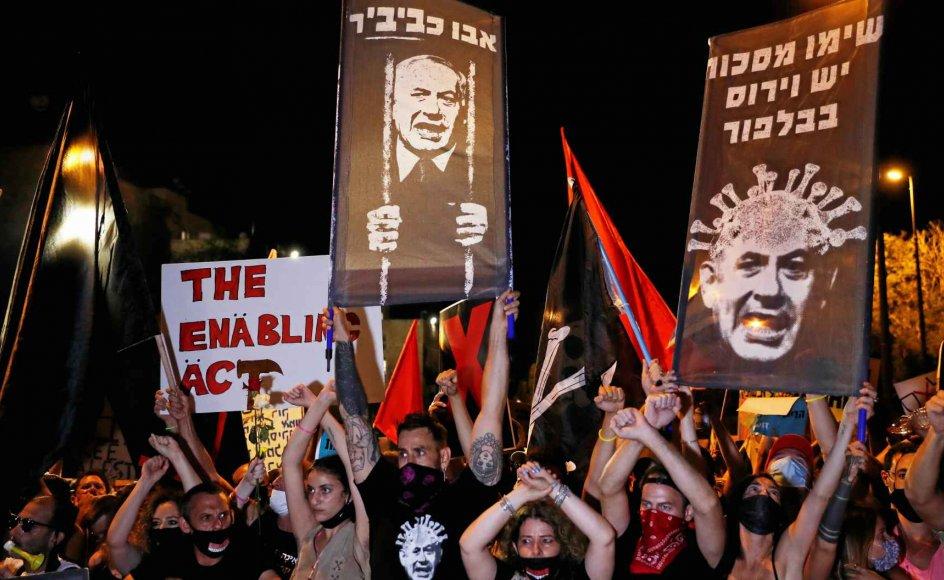 """I ugevis har demonstranter protesteret foran Benjamin Netanyahus embedsbolig Balfourgaden i Jerusalem i protest mod regeringens corona-håndtering. Her bliver den korruptionstiltalte premierminister blandt andet selv fremstillet som en virus, som når der på skiltet står """"Tag ansigtsmaske på, der er en virus i Balfour"""". – Foto: Ronen Zvulun/Reuters/Ritzau Scanpix."""