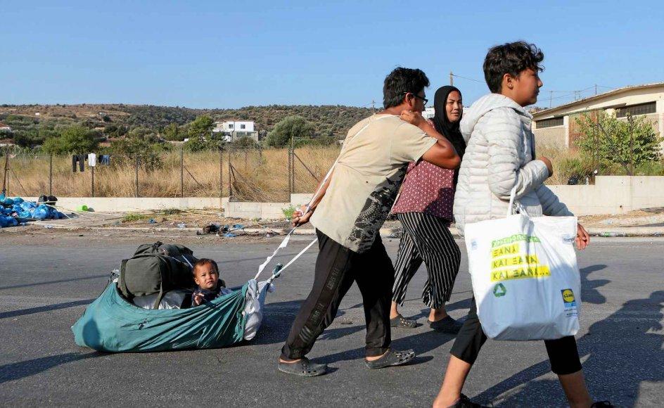 Beboere fra den nedbrændte Moria-lejr på græske Lesbos bevæger sig mod en ny, midlertidig lejr. Hvis det står til den socialdemokratiske regering, skal asylansøgere ikke længere befinde sig i Europa, mens deres sager bliver behandlet. – Foto: Elias Marcou/Reuters/Ritzau Scanpix.