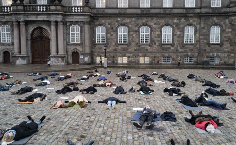 På våde og kolde brosten demonstrerede cirka 50 yogalærere i tirsdags på Christiansborg Slotsplads. Demonstrationen foregik i absolut stilhed i stillingen shavasana, der kan oversættes til død mands stilling. – Foto: Mikkel Møller Jørgensen