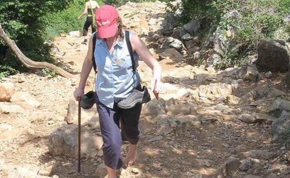 Midlet helliger målet. Mange katolikker vælger at bestige bjergene ved Medjogorje med skoene bundet om halsen, fordi turen så bliver mere lidelsesfuld. På den måde er det nemmere at forstå, hvordan Jesus led på jorden, lyder forklaringen.  -- Foto: Dorthe Hein Løwendahl.
