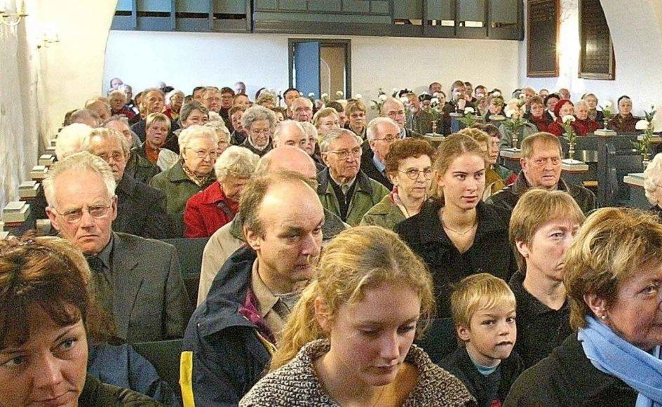 """Selvom der var mange kirkegængere i Kibæk Kirke ved Herning, da fotografen lagde vejen forbi, så er danskernes kirkegang generelt ikke noget at prale af. Mere end tre fjerdedele af befolkningen går """"aldrig"""" eller """"sjældent"""" i kirke. –"""